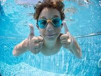Image of a boy swimming underwater with his thumbs up