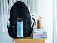 Image of school bag and face mask on a desk