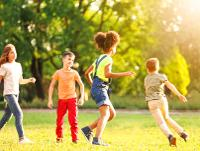 Image of children playing outside in the sunshine
