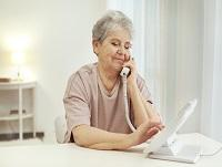 Elderly woman dialling telephone at home