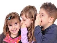 Image of three children whispering