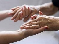 Image of younger hands holding older hands