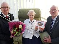 Image of Ethel Cadwallader being presented with a card and bouquet