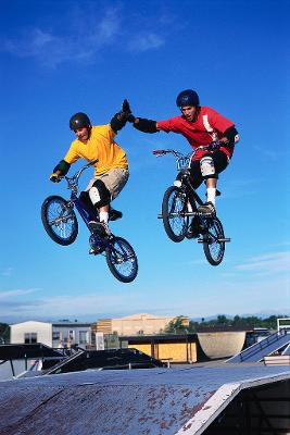 Image of two young people on bikes in a skate park