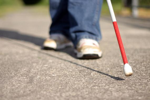 Image of a person walking with a white cane