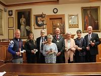Image of a group of people receiving awards from the former Chairman of Powys County Council