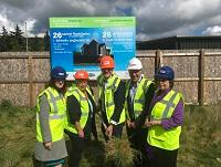 Image of people at turf-cutting ceremony in Newtown