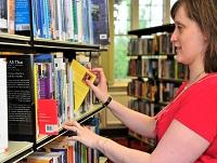 Image of librarian putting a book on the shelf