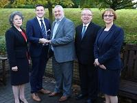 Image of a group of people watching Cllr James Evans receive an trading standards award